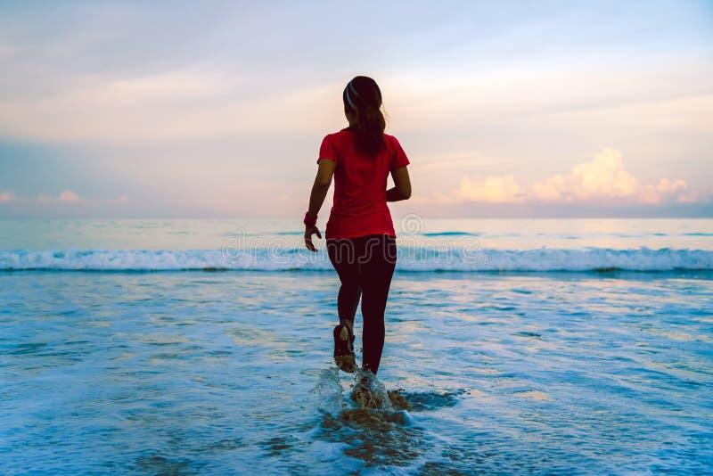 Laufendes Training des Mädchens, das morgens auf dem Strand rüttelt entspannen Sie sich und glücklich mit dem Laufen auf dem Meer stockfotografie