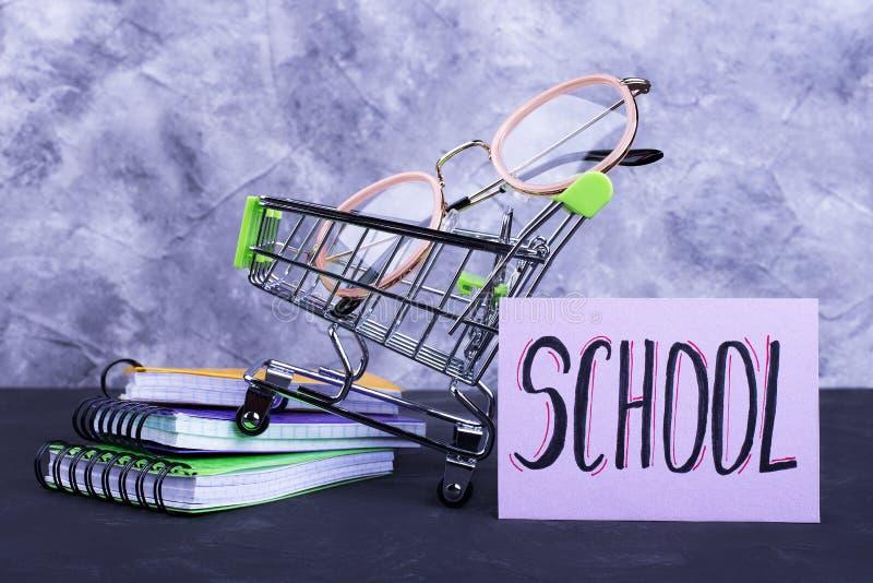 Laufkatze mit Gläsern, Notizbücher, Aufschrift Schule stockbild