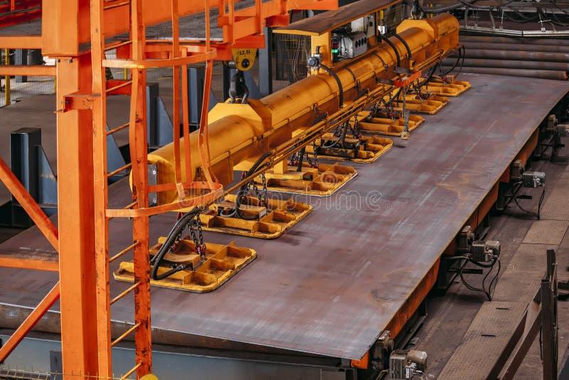 Laufkran mit dem Vakuum, das die Greifer anheben Eisenblätter behandelt stockfotos