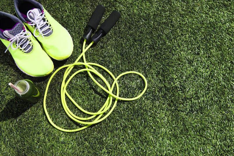 Laufschuh-, Seilspringen- und Getränkflasche mit grünem Saft stockbilder