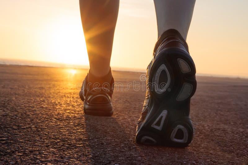 Laufschuhe im Asphalt mit Sonnenuntergang stockfotos