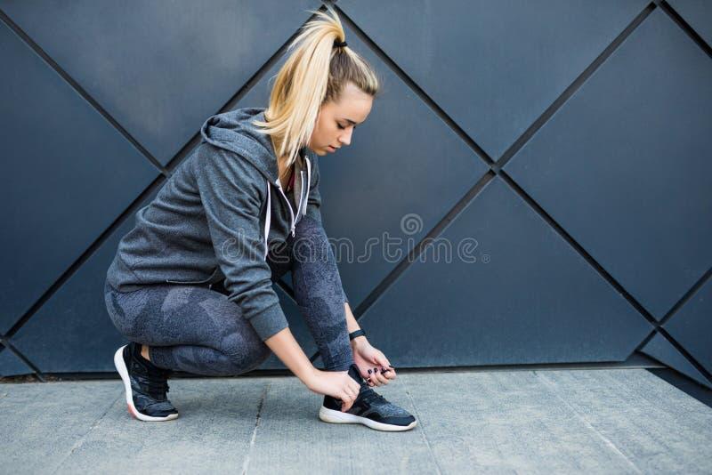 Laufschuhe - Nahaufnahme der Frau Schnürsenkel binden Weiblicher Sporteignungsläufer, der zu draußen rütteln fertig wird lizenzfreie stockfotografie