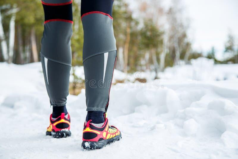 Laufschuhe - Nahaufnahme des weiblichen Sporteignungsläufers, der zu im Winter draußen rütteln fertig wird lizenzfreie stockfotos