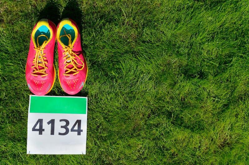 Laufschuhe und Marathonlaufschellfisch (Zahl) auf Grashintergrund, Sport, Eignung und gesundem Lebensstil stockfotografie