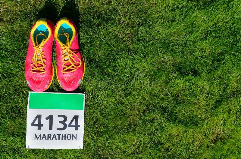 Laufschuhe und Marathonlaufschellfisch (Zahl) auf Grashintergrund, Sport, Eignung und gesundem Lebensstil stockfotos