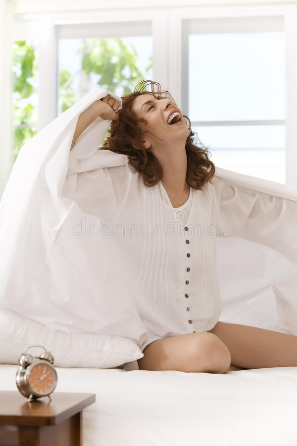 Laugh. Portrait of nice young woman waking up in her bedroom stock photo
