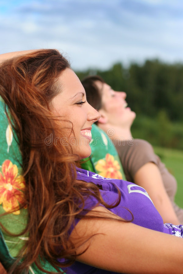 Laugh. Two young girls relaxing outdoors royalty free stock photos