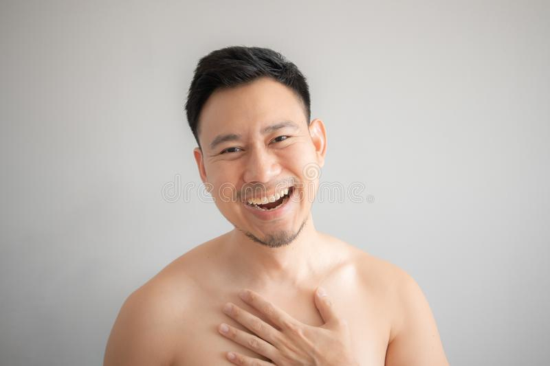 Laugh face of Asian man in topless portrait isolated on gray background royalty free stock photography
