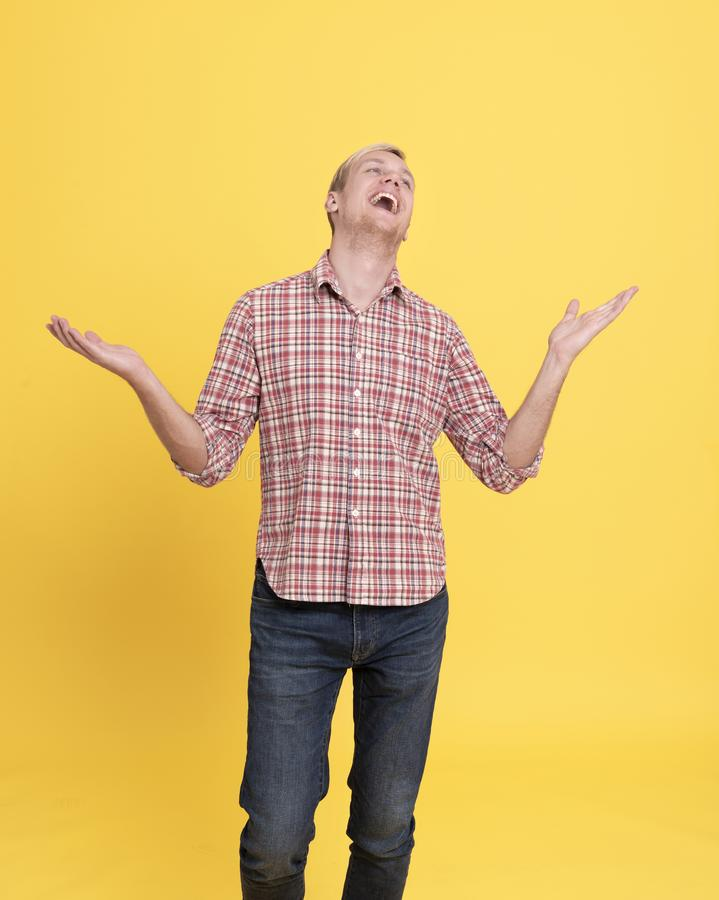 Laugh young man wearing red plaid shirt standing isolated over yellow background.  royalty free stock image