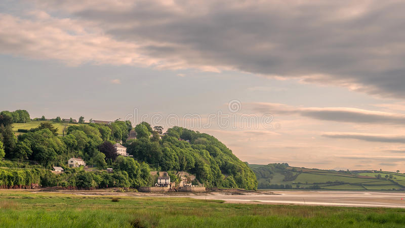 Laugharne Taf Estuary Wales. Landscape view the tidal estuary with The Boathouse, The Writing Shed and other houses and fields as the focus royalty free stock photo