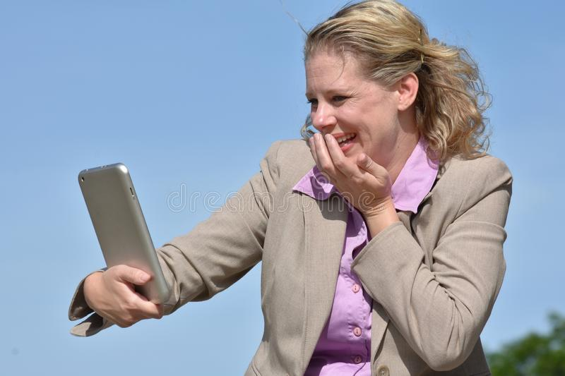 Laughing Adult Blonde Business Woman With Tablet royalty free stock image