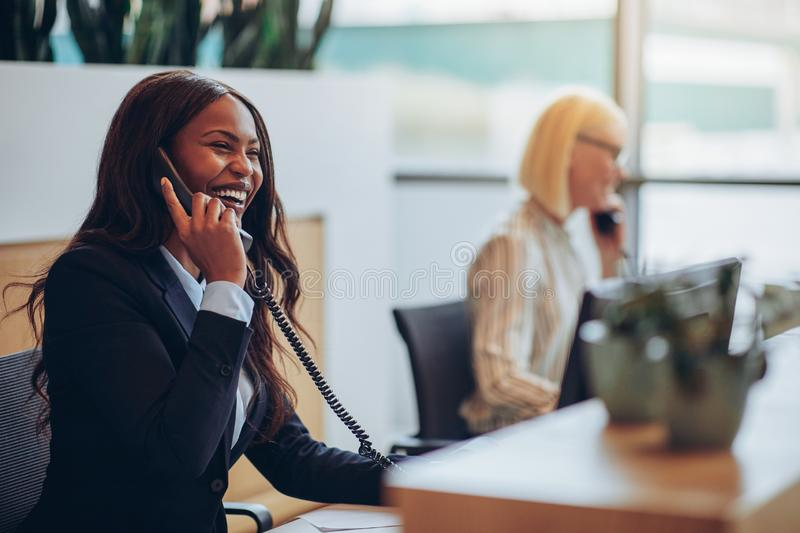 Laughing African American businesswoman working at an office rec royalty free stock images