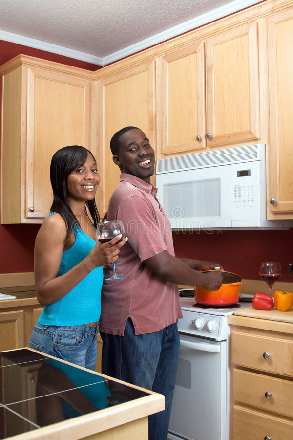 Laughing African American Couple Cooking-Vertical. Attractive young laughing African American couple cooking dinner together and drinking red wine. Vertically royalty free stock images