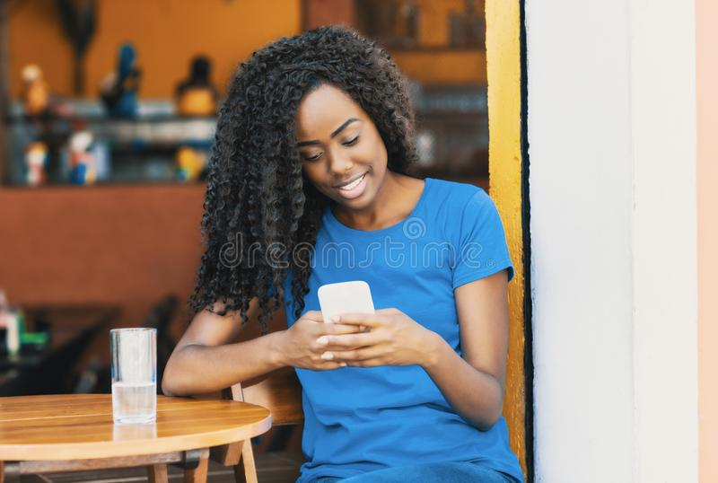 Laughing african american woman at bar texting message with mobile phone royalty free stock images
