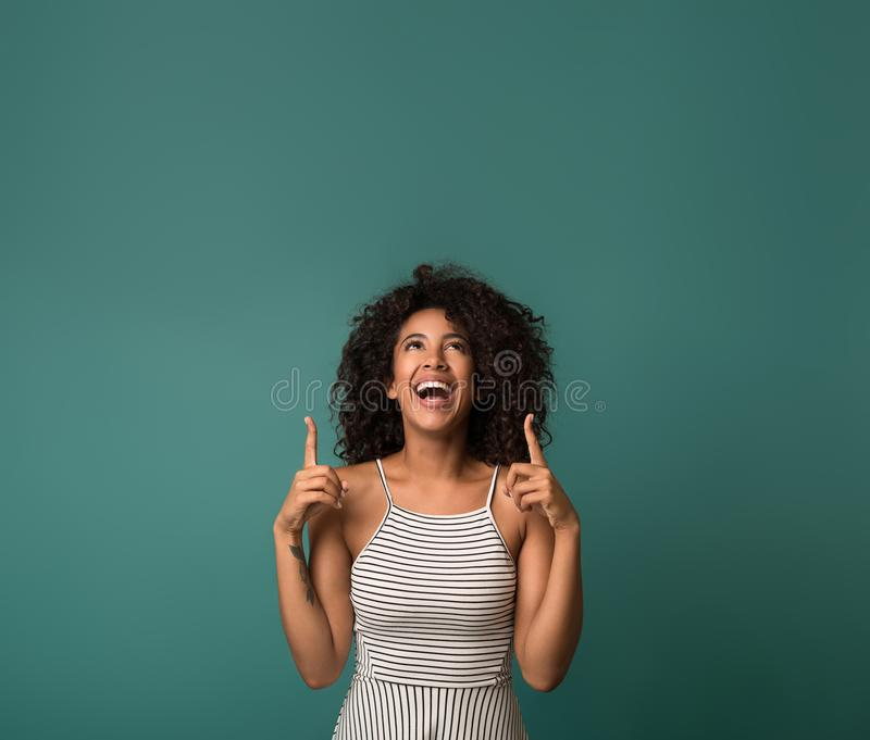 Laughing african-american woman pointing fingers upward, copy space royalty free stock photos