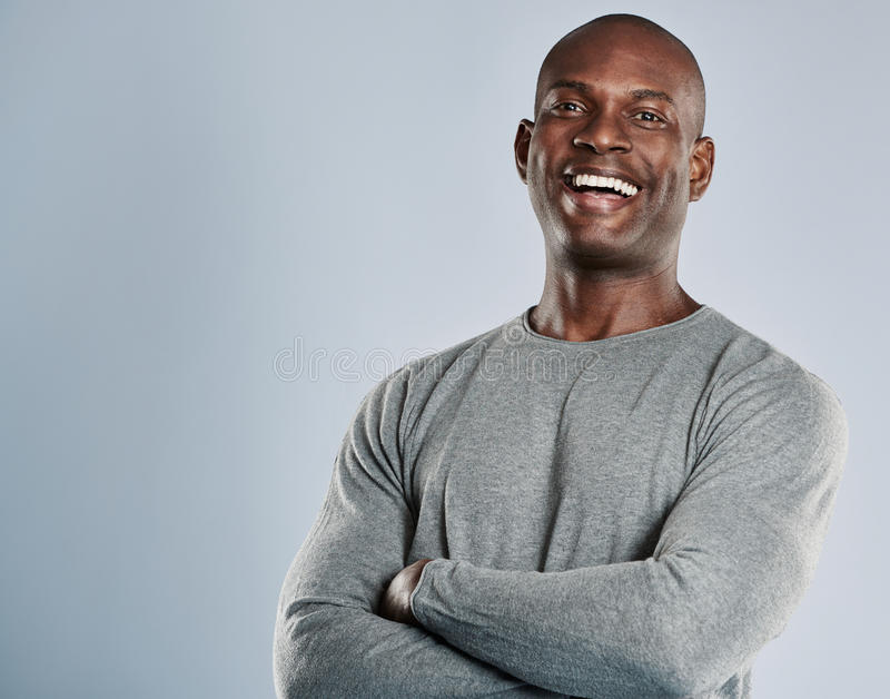 Laughing African man in gray shirt with copy space. Laughing single handsome young African man with bald head in gray long sleeve shirt and folded arms over royalty free stock photos