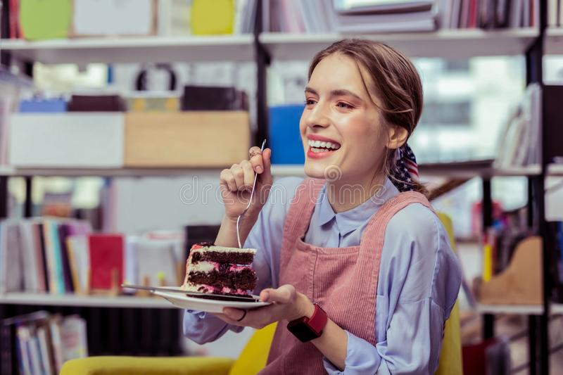 Laughing appealing girl separating piece of cake with fork. Shocked with taste. Laughing appealing girl separating piece of cake with fork and desiring a bite stock photos
