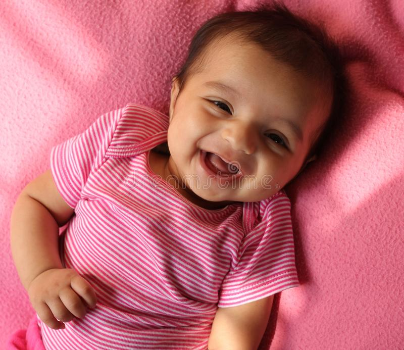 Laughing asian baby girl in pink cloths stock photos