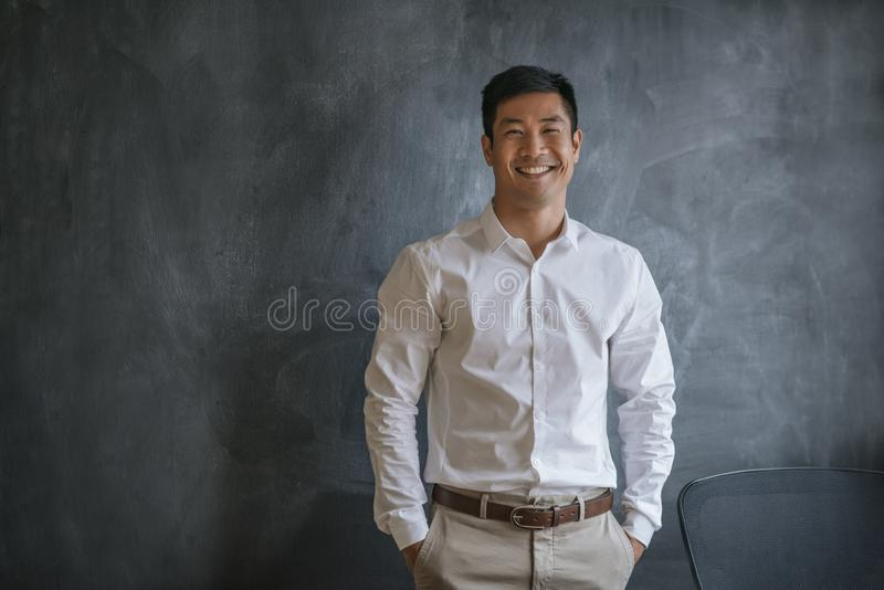 Laughing Asian businessman standing in front of a blank chalkboard stock photography