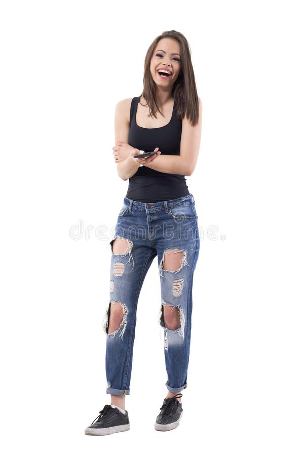 Laughing attractive latin beauty woman in casual clothes holding mobile phone and looking at camera. stock image