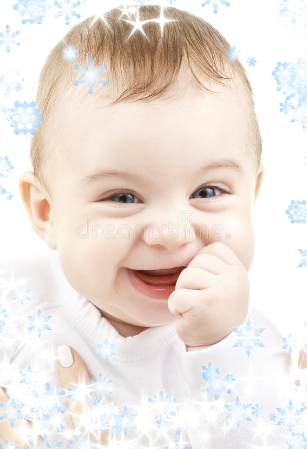 Laughing baby. Bright closeup portrait of adorable baby with snowflakes royalty free stock photos