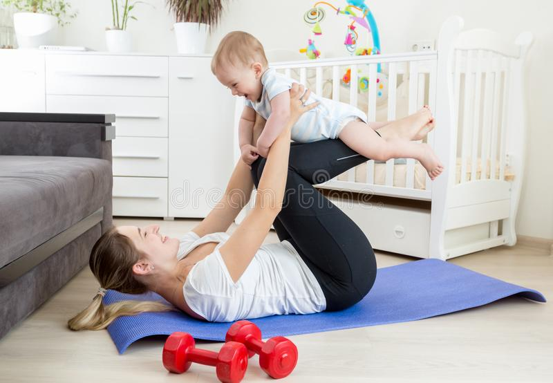 Happy laughing baby boy exercising with mother on yoga mat at home. Laughing baby boy exercising with mother on yoga mat at home stock images