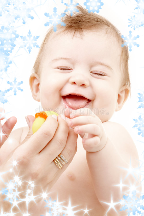 Laughing baby boy in mother hands with rubber duck royalty free stock image