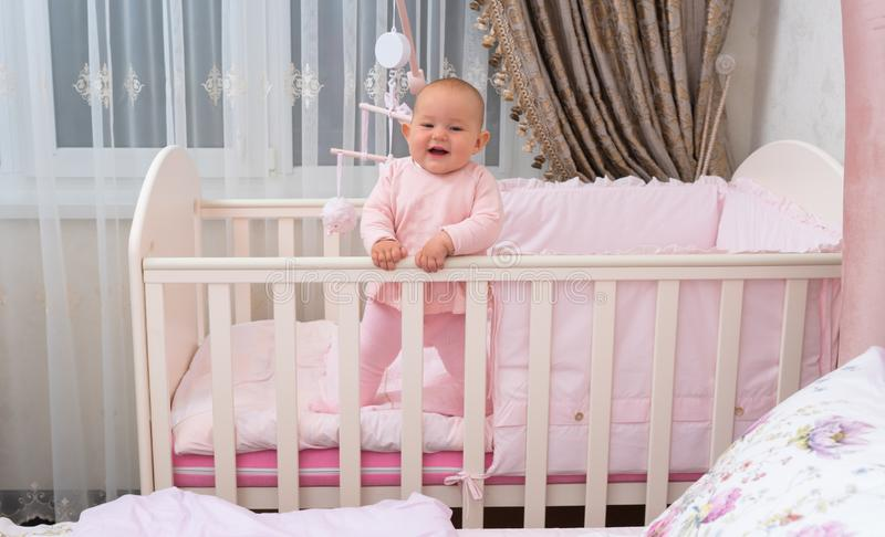 Laughing baby in crib in pink bedroom scene. royalty free stock images