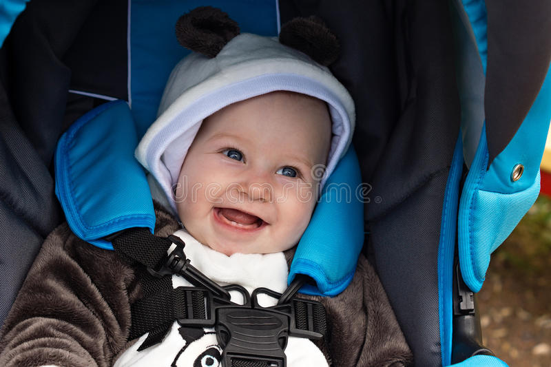 Laughing baby in stroller stock photo