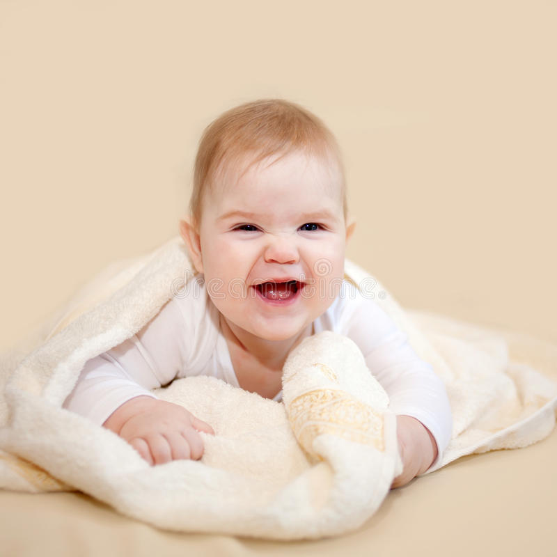 Laughing baby wrapped in towel after bath royalty free stock photography