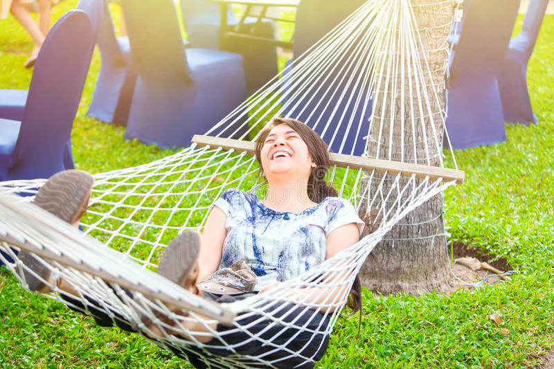 Laughing biracial teen girl relaxing in hammock royalty free stock image
