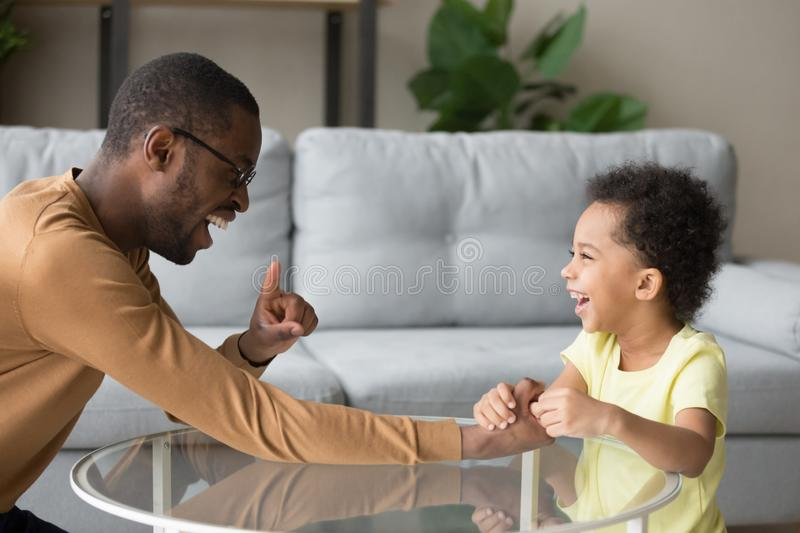 Black father laughing playing with small kid at home stock images