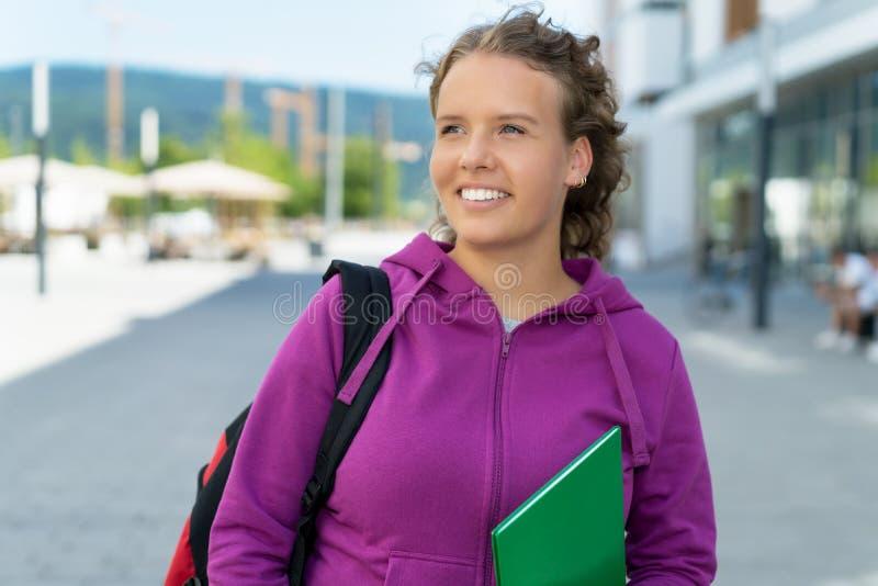 Laughing blond female student walking to university royalty free stock photo