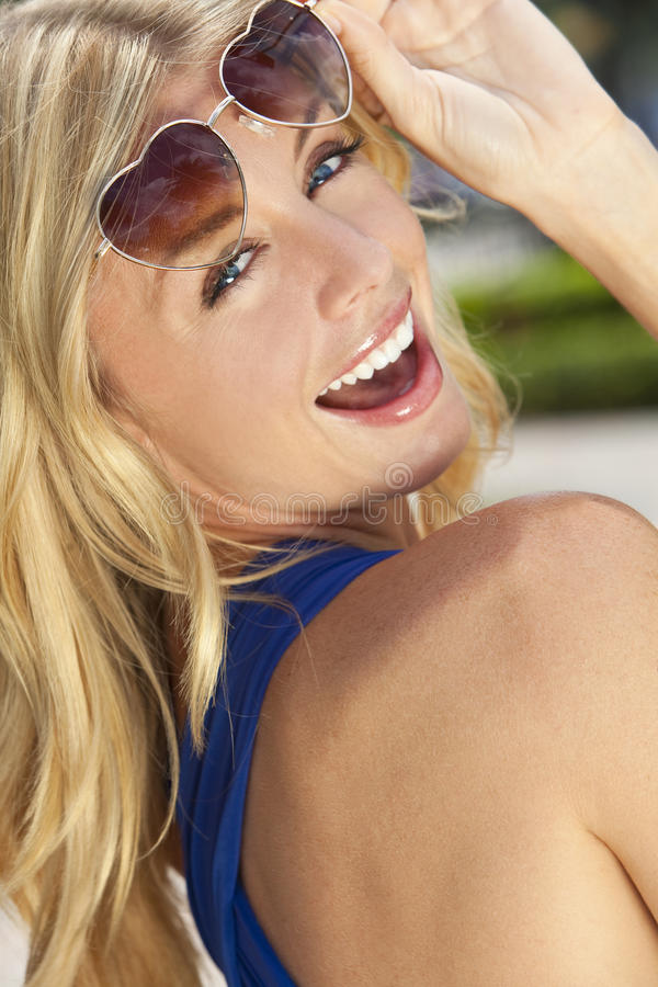 Laughing Blond Woman In Heart Shaped Sunglasses royalty free stock photography