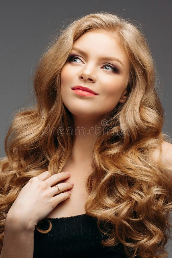 Laughing blonde girl with long and shiny wavy hair . Beautiful smiling woman model with curly hairstyle . stock image