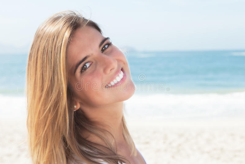 Laughing blonde woman at beach looking at camera stock image