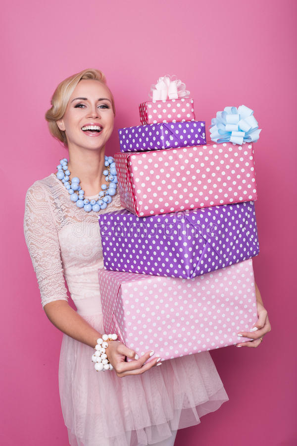 Laughing blonde woman holding big and small colorful gift boxes. Soft colors. Christmas, birthday, Valentine day, presents stock photos
