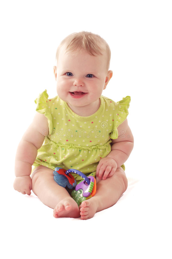 Laughing blue eyed baby sits with her toy rattle. Laughing 6 month old baby girl with big blue eyes and ruffled dress sits with a rattle. Pastels, isolated on royalty free stock photo