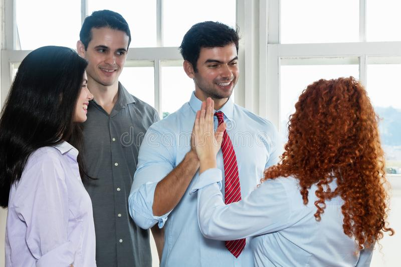 Laughing boss giving high five to employee stock photos