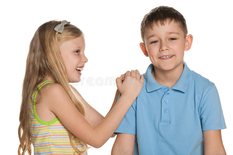 Laughing boy and girl are standing together. On the white background royalty free stock photo