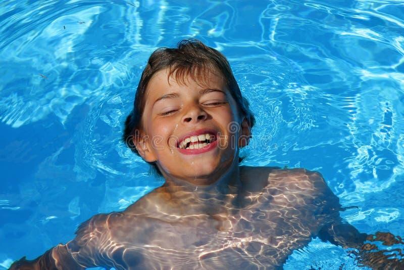 Laughing boy having fun in swimming pool stock image