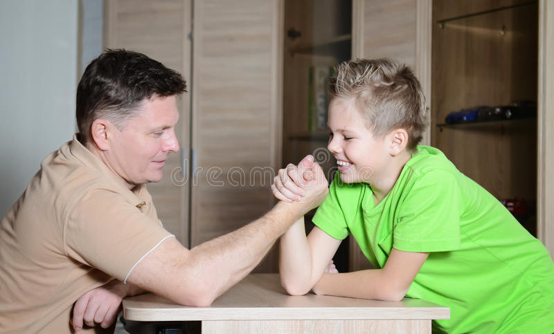 Laughing boy and his dad competing in physical strength. Father arm wrestling with his son - happy family time together. Photo of boy and his dad competing in stock photos