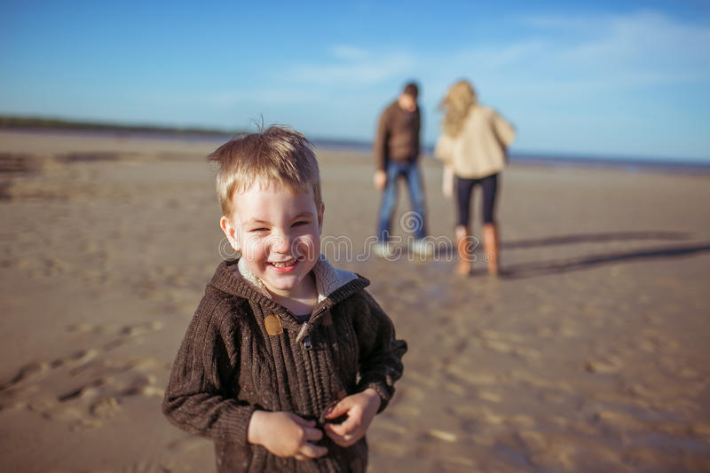 A laughing boy and his parent in the background stock images
