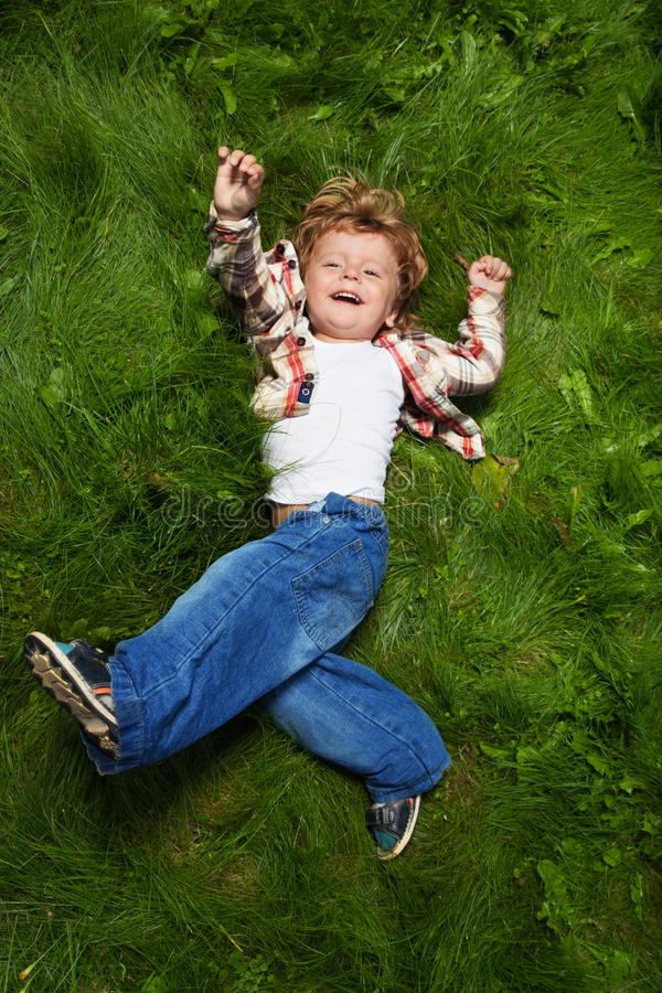 Laughing boy rolling on grass. Laughing boy rolling on emerald grass stock photos