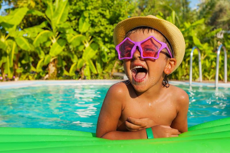 Laughing boy in star-shaped sunglasses on airbed. Laughing boy in star-shaped sunglasses on green airbed in the swimming pool outside in summer royalty free stock image