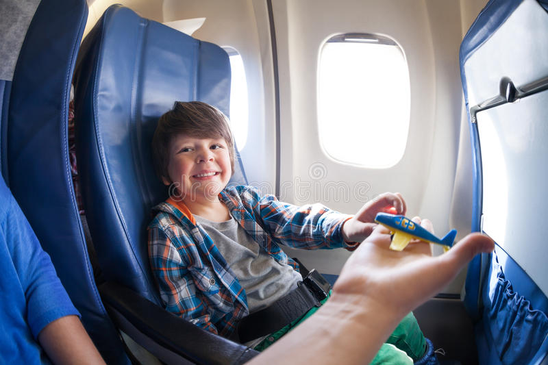 Laughing boy take toy plane, sit in jet airplane. Happy laughing boy sits by the window in the airplane and take toy plane from the mothers hand royalty free stock image