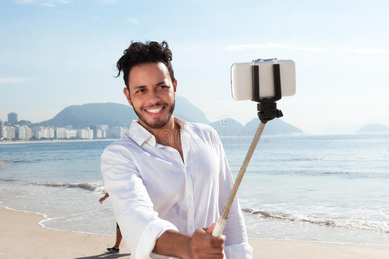 Laughing brazilian man making picture with a selfie stick at Copacabana beach. At Rio de Janeiro with ocean in the background royalty free stock image