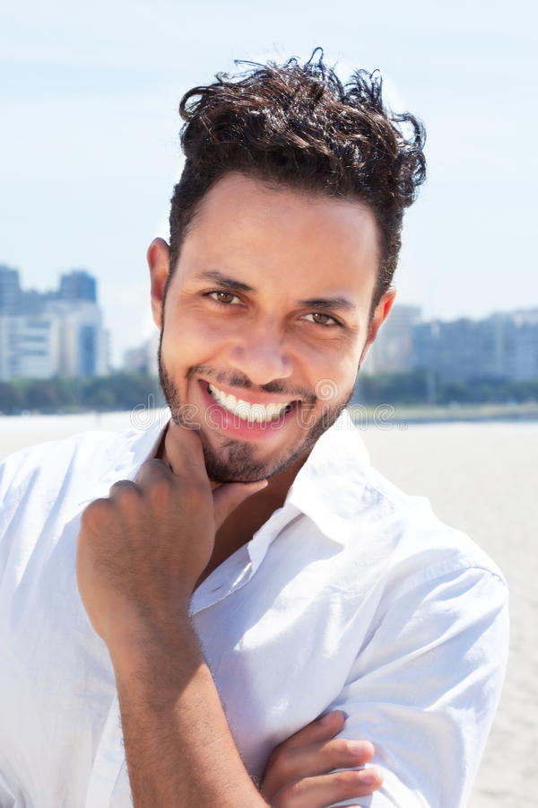 Laughing brazilian man with skyline in the background. Laughing brazilian man laughing at camera with blue sky and skyline of a modern city in the background stock photos