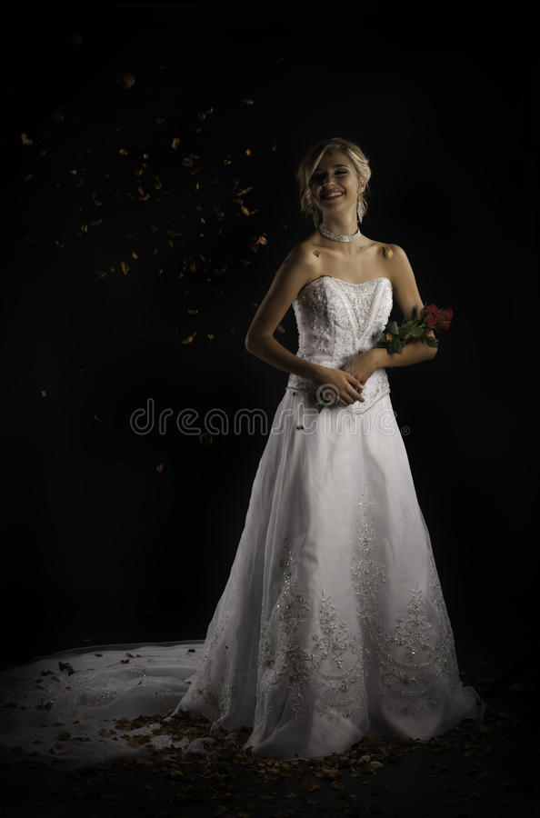 Laughing bride being thrown with rose petals while holding bouquet royalty free stock photo