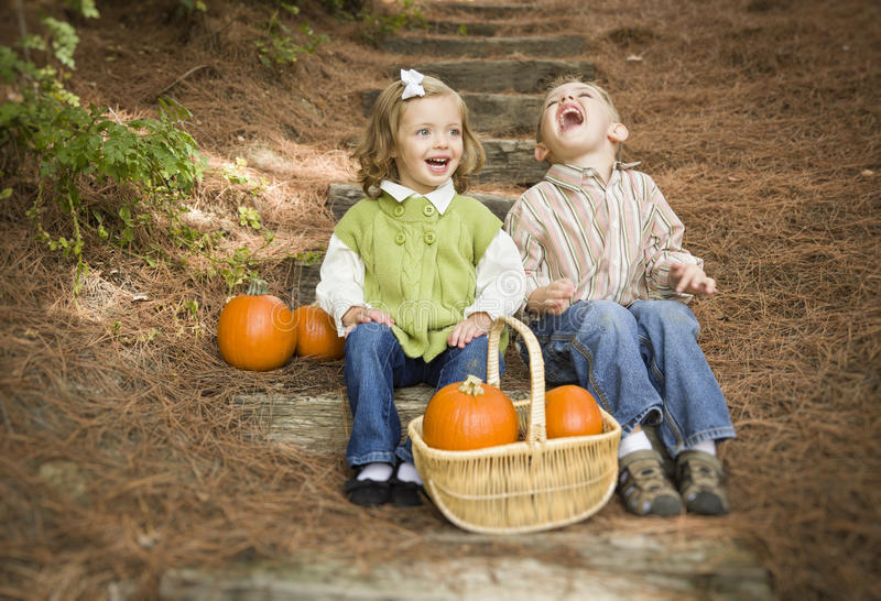 Laughing Brother and Sister Children Sitting on Wood Steps with Pumpkins royalty free stock photo